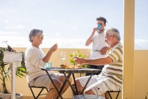 Mature and young family people enjoy time together with drinks and food outdoor at home